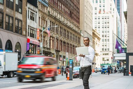 Young African American businessman traveling, working in New York, wearing white shirt, black pants, holding laptop computer, walking on street, looking down, reading. Cars, buildings on background.