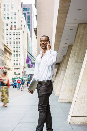 Young African American businessman traveling, working in New York, wearing white shirt, black pants, carrying laptop computer, walking out from office building, talking on cell phone, smiling.