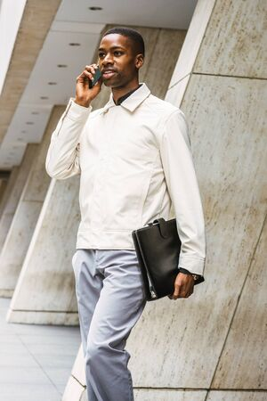 Young African American businessman traveling, working in New York, Young black man wearing light color jacket, carrying leather briefcase, walking out from office building, talking on cell phone.
