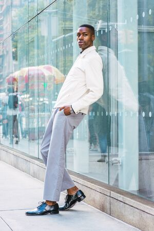 Young African American Man relaxing on street in New York. Young black man wearing light color jacket, gray pants, leather shoes, standing against glass wall on street in Manhattan, New York, relaxing