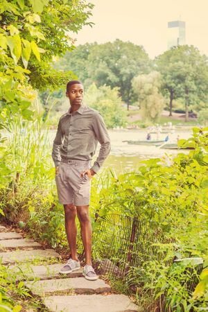 Young African American Man waiting for you at Central Park in New York. Young black man wearing gray shirt, shorts, sneakers, standing on narrow stone road by lake. People rowing boats on background.