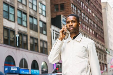 Young African American Man traveling in New York. Young black man wearing light color jacket, walking on street with high buildings in Manhattan, talking on cell phone.