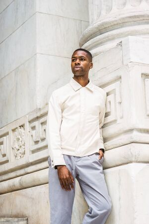 Portrait of Young Handsome African American Man in New York. Young black man wearing light color jacket, standing against vintage marble wall, looking around, relaxing,  thinking.