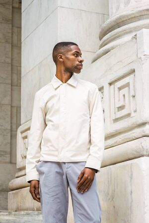 Portrait of Young Handsome African American Man in New York. Young black man wearing light color jacket, standing by vintage marble wall, looking, thinking, lost in thought. 版權商用圖片 - 129324987