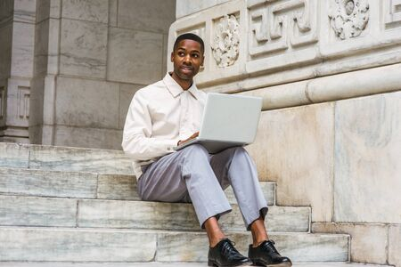 Way to Success. African American Student wearing light color jacket, gray pants, black leather shoes, sitting on stairs of office building on campus in New York, studying, working on laptop computer. 版權商用圖片 - 129324985
