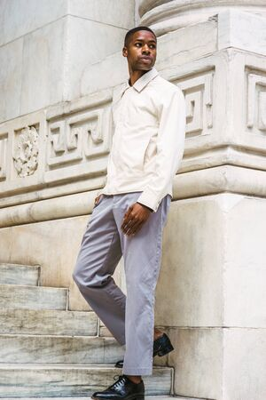 Young Handsome African American Man wearing light color jacket, gray pants, black leather shoes, standing on stairs by vintage marble wall on campus in New York, turning around, looking away.
