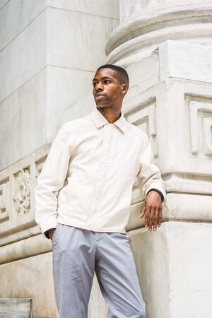 Portrait of Young Handsome African American Man in New York. Young black man wearing light color jacket, standing by vintage marble wall, looking around, relaxing,  thinking. 版權商用圖片