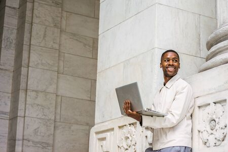 Happy Young African American Man studying in New York. Young black student wearing light color jacket, standing against vintage wall on campus, working on laptop computer, looking up, smiling. 版權商用圖片 - 129324994
