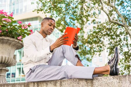 Young African American Man reading book outside. Young black man wearing light color jacket, gray pants, leather shoes, sitting on top of half wall by street in Manhattan, New York, reading red book.