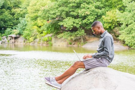 Young African American Man wearing long sleeve gray shirt, shorts, sneakers, crossing legs, sitting on rocks by lake at Central Park, New York, looking down, typing, working on laptop computer. 版權商用圖片