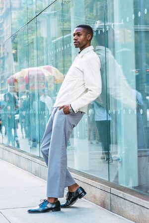 Young African American Man relaxing on street in New York. Young black man wearing light color jacket, gray pants, leather shoes, standing against glass wall on street in Manhattan, New York, relaxing 版權商用圖片 - 129324870