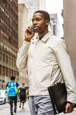 Young African American businessman traveling, working in New York, Young black man wearing light color jacket, carrying leather briefcase, walking on street in Manhattan, talking on cell phone. Stockfoto