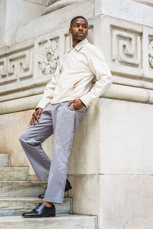 Portrait of Young Handsome African American Man in New York. Young black man wearing light color jacket, gray pants, black leather shoes, standing against vintage marble wall, looking around, relaxing 版權商用圖片
