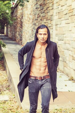 Young East Indian American Man wearing black long hooded outwear, opened, showing half naked strong body, black jeans, forcefully walking up along rock wall in New York, looking forward. Stock fotó