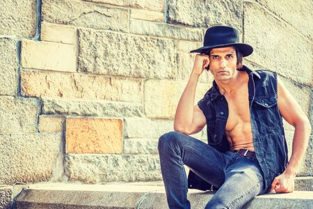 Young East Indian American Man wearing black sleeveless fashionable Denim jacket, unbuttoned, showing half naked body, jeans, Fedora hat, sitting on stone fence by rock wall in New York, thinking