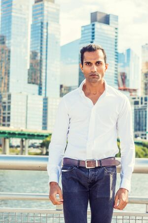 Young East Indian American Man wearing white shirt, black jeans, standing in business district with high buildings by Hudson River in New York, looking forward. 版權商用圖片 - 129324804
