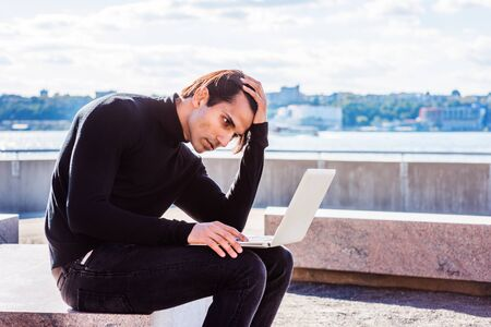 Young East Indian American Man wearing black knit pull over sweater, sitting on stone bench at park in New York under sun, working laptop computer, hand touching head, looking down, thinking. Stock Photo