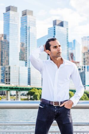Young East Indian American Man wearing white shirt, black jeans, standing in business district with high buildings by Hudson River in New York, hand on back of head, looking around, thinking.