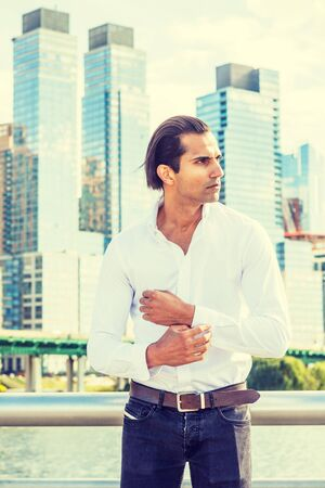 Young East Indian American Man wearing white shirt, black jeans, standing in business district with high buildings by Hudson River in New York, hand touching cuff, looking away. 版權商用圖片