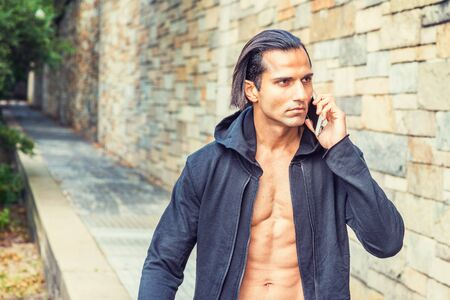 Young East Indian American Man wearing black hooded outwear, opened, showing half naked body, talking on cell phone, walking on narrow road with rock wall in New York.