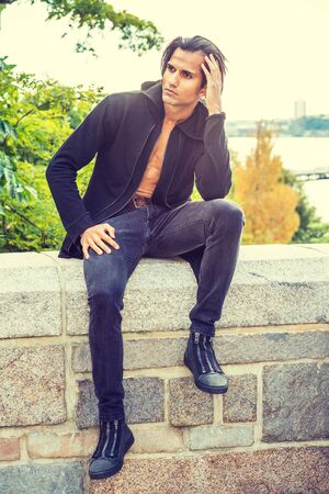 Young Modern East Indian American Man wearing black long hooded outwear, opened, black jeans, sneakers, sitting on stone fence by Hudson Rive in New York, hand touching head, relaxing, thinking. 写真素材