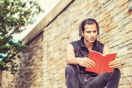 Young Modern East Indian American Man wearing black sleeveless jacket, jeans, sitting by stone wall at park in New York, hand holding red book, looking down, reading, relaxing. 스톡 콘텐츠
