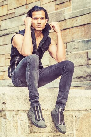 Young Modern East Indian American Man wearing black sleeveless jacket, jeans, sneakers, sitting on stone fence by stone wall at park in New York, relaxing, thinking.