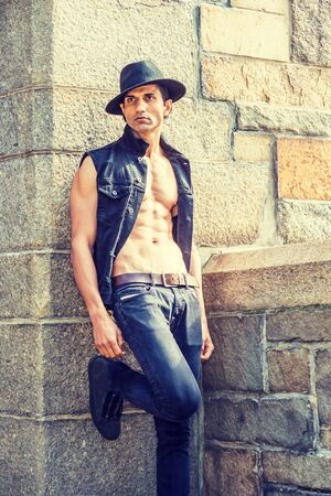 Young East Indian American Man wearing black sleeveless fashionable Denim jacket, unbuttoned, showing half naked body, jeans, Fedora hat, standing by rock wall and fence in New York, looking away. 스톡 콘텐츠