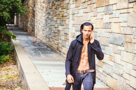 Young East Indian American Man wearing black long hooded outwear, opened, showing half naked strong body, black jeans, talking on cell phone, forcefully walking up along rock wall in New York.