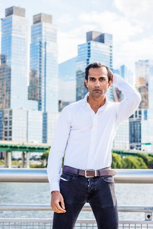 Young East Indian American Man wearing white shirt, black jeans, standing in business district with high buildings by Hudson River in New York, hand on back of head, looking forward. 版權商用圖片