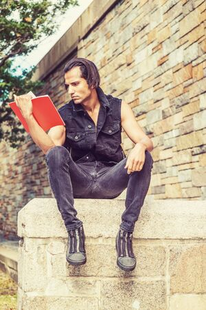 Young Modern East Indian American Man wearing black sleeveless jacket, jeans, sneakers, sitting on stone fence by stone wall at park in New York, looking down, reading red book. 스톡 콘텐츠