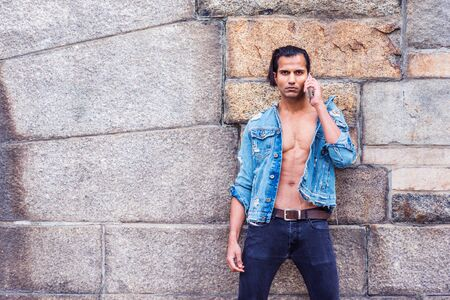 Young East Indian American Man wearing blue fashionable Denim jacket, opened, showing half body, black jeans, standing against rock wall in New York, seriously talking on cell phone.