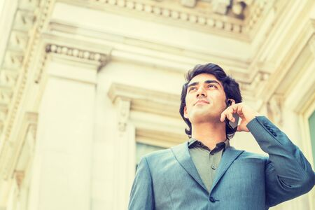 Young Mix Race American Businessman working in New York City, wearing dark blue jacket, green undershirt, standing outside old style office building, looking up, calling on cell phone, thinking. 版權商用圖片