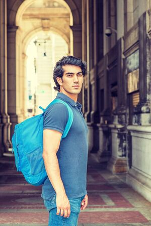 Back to School. Mix Race American college student wearing blue short sleeve shirt, jeans, shoulder carrying back bag, standing on street on campus in New York City, coming back from summer vacation