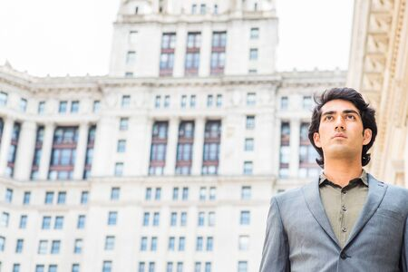 Portrait of Young Mix Race American College Student studying in New York City. Young Man wearing dark blue jacket, green undershirt, standing outside vintage office building, confidently looking up.