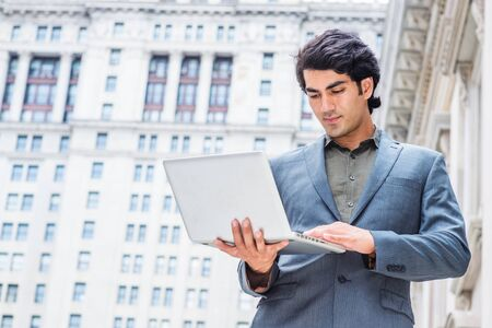 Way to success. Young Mix Race American College Student studying in New York City, wearing dark blue jacket, standing outside old style office building, looking down, working on laptop computer. 版權商用圖片