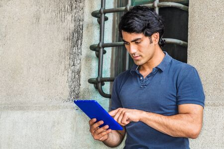 Modern Reading. Young Mix Race American College Student studying in New York City, wearing blue short sleeve shirt, siting against wall with window on street in campus, reading blue tablet computer. 版權商用圖片