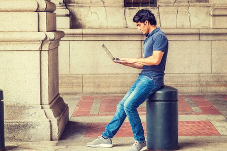 Way to success. Young Mix Race American College Student studying in New York City, wearing blue short sleeve shirt, jeans, sneakers, sitting on street, looking down, working on laptop computer.