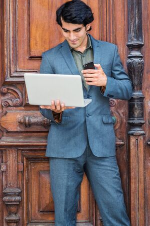 Young Mix Race American Businessman working in New York City, wearing dark blue jacket, pants, green undershirt, standing by old style office doorway, holding on cell phone, reading on laptop computer. 版權商用圖片 - 129324516