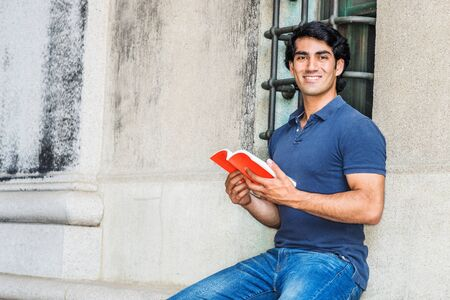 I love reading book. Young American College Student studying in New York City, wearing blue short sleeve shirt, sitting against wall with window on street in campus, holding red book, smiling.