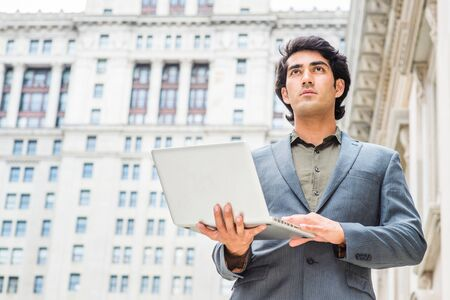 Way to success. Young Mix Race American College Student studying in New York City, wearing dark blue jacket, standing outside old style office building, working on laptop computer, looking, thinking.
