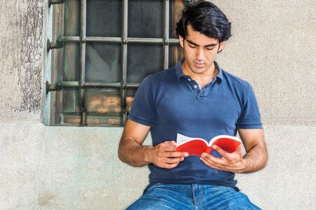 I love reading book. Young Mix Race American College Student studying in New York City, wearing blue short sleeve shirt, jeans, sitting against wall with window on street in campus, reading red book. 版權商用圖片 - 129324534