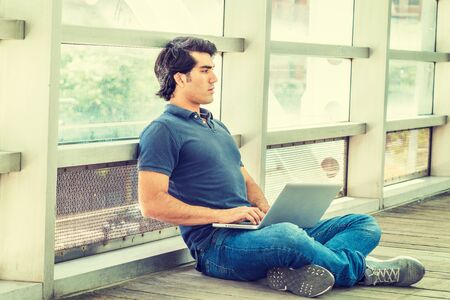 Young American College Student studying in New York City, wearing blue short sleeve short, jeans, sneakers, sitting cross legged on floor against glass wall on campus, working on laptop computer.