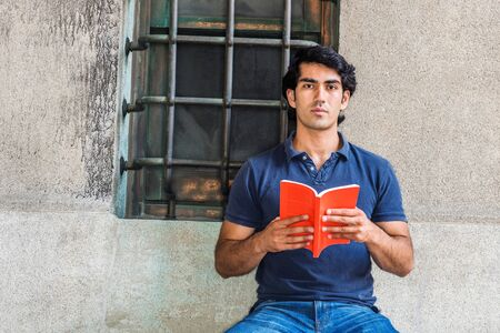 I love reading book. Young American College Student studying in New York City, wearing blue short sleeve shirt, sitting against wall with window on street in campus, holding red book, thinking. Standard-Bild