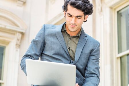 Way to success. Young Mix Race American College Student studying in New York City. Man wearing dark blue jacket, siting outside old style office building, looking down, working on laptop computer. 版權商用圖片