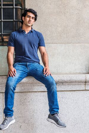 Portrait of Young Mix Race American College Student in New York City, wearing blue short sleeve shirt, blue jeans, sneakers, sitting against old style wall on street in campus, relaxing, thinking.