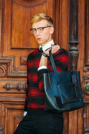Young blonde American male college student wearing patterned red, black knit sweater, glasses, holding leather bag on shoulder, standing by brown vintage wooden office door, looking at you.