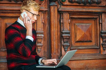 Young blonde American college student wearing patterned red, black knit sweater, glasses, sitting by brown vintage wooden office door, working on laptop computer, talking on cell phone. Фото со стока