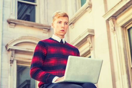 Young blonde American college student wearing patterned red, black knit sweater,  sitting outside vintage office building on campus, working on laptop computer, looking up, thinking.