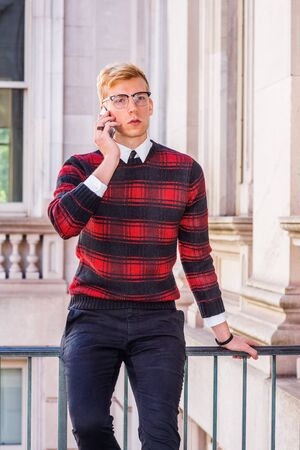 Young blonde American college student wearing patterned red, black knit sweater, glasses, sitting by railing in vintage office building in New York, talking on cell phone.